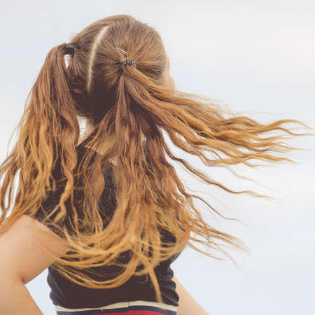 Teenage girl having brown ponytails windblown tousled hair. Unrecognizable woman having outdoor fun. Stock Photo
