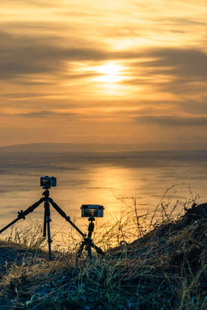 Professional camera taking picture film video of sunrise over sea surface, Greece Peloponnese Mani Peninsula.