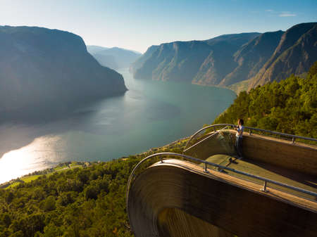 Aerial view. Tourist woman with camera enjoying fjord view Aurlandsfjord landscape from Stegastein viewing point. Norway Scandinavia. National tourist route Aurlandsfjellet.