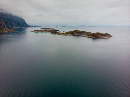 Sea landscape with yacht boat and stone islets among the waters of fjord Vjestfjord, Lofoten islands, Henningsvaer region, Norway. Hazy day, overcast weather. 写真素材