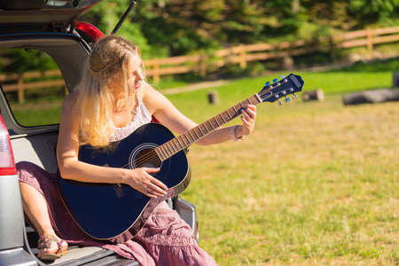 Hippie looking woman wearing long skirt sitting in van vehicle camper trailer with guitar, playing peacefully music surrounded by nature. Female camping, traveling, hitchhiking Reklamní fotografie