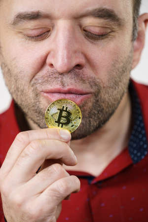 Adult man having bitcoin coin in hand. Crypto internet currency banking concept.