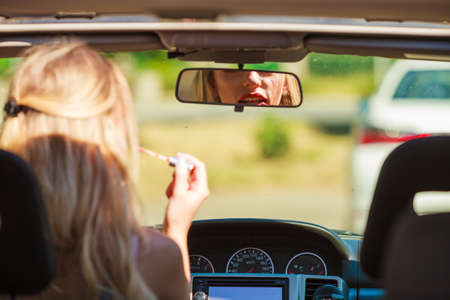 Concept of danger auto drive. Young woman driver painting her lips doing applying make up while driving the car.
