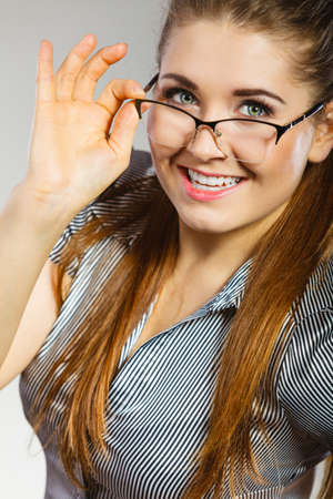 Close up portrait of happy business woman wearing eyeglasses and grey shirt. Stock Photo