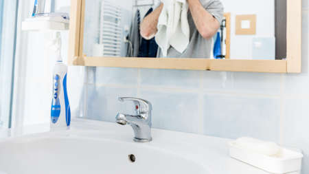 Clean white bathroom sink with oral hygiene essentials, in foreground man drying his face using clean towel