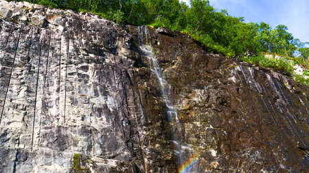 Little waterfall in rocky mountains near the parking at Ornesvingen viewpoint, Geiranger, Norway. Imagens