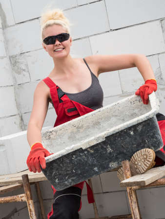 Woman wearing workwear working on construction site. Mixing cement in bowl preparing mortar. Partially built new home early stage. Industry. Stok Fotoğraf