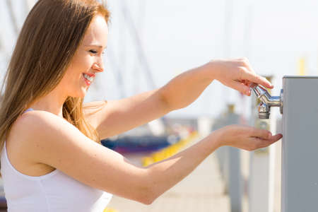 Woman drinking clean water from tap in marina. Reklamní fotografie - 124766311