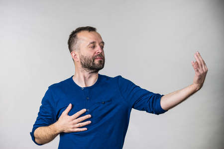 Man pretending acting be or not to be gesturing with hand. Adult guy having fun, playing theater play Stock Photo