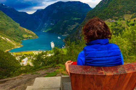 Tourism vacation and travel. Female tourist enjoying beautiful view over magical Geirangerfjorden from Flydalsjuvet viewpoint, Norway. Tourist attraction. 写真素材