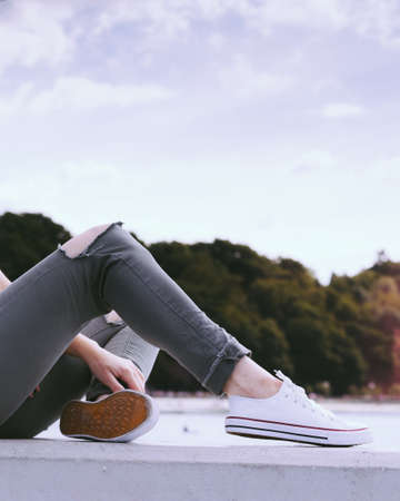 Trendy fashionable unrecognizable woman relaxing outdoor wearing casual footwear white sneakers and hole trousers