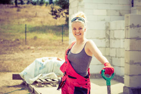 Woman worker using shovel standing on industrial construction site, working hard on house renovation. Stok Fotoğraf