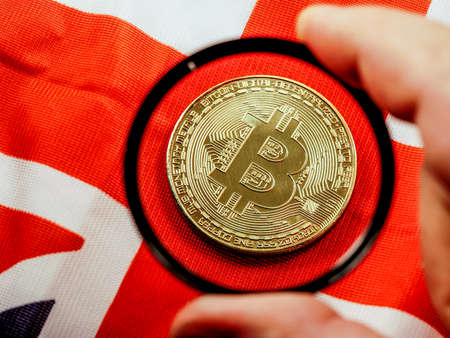 Male hand holding magnifying glass looking on new virtual money btc bitcoin placed on British United Kingdom Union Jack flag background. Crypto currency, blockchain business concept.