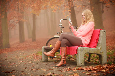 Technology smartphone nature outdoor cycling concept. Smiling girl listening to music. Young lady in park sitting on bench next to bike enjoying sound wearing headphones.
