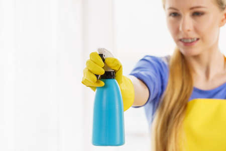 Young woman in yellow gloves cleaning window pane at home with spray detergent. Cleaning concept