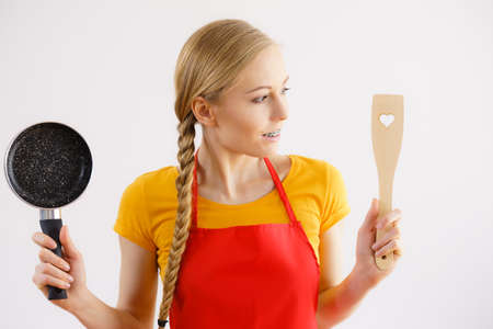 Happy cheerful young woman wearing apron holding small cooking pan and wooden spatula about to cook in kitchen.