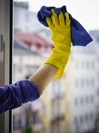 Person using cloth cleaning detergent to clean window glass. House clean products, household care equipment. Stock Photo