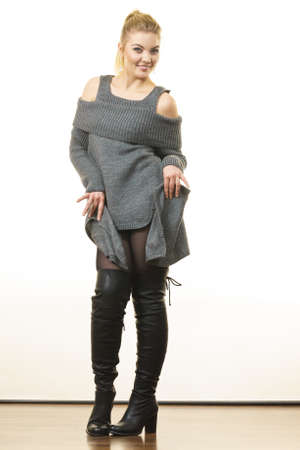 Woman in ponytail wearing gray long top sweater tunic, black tights. Stylish, autumnal outfit. Stock Photo