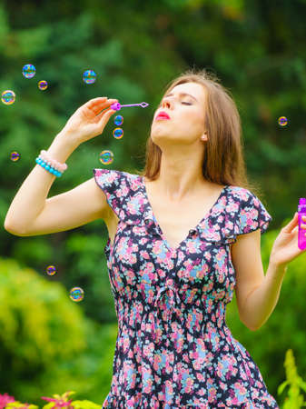 Happiness and carefree concept. Young woman having fun blowing soap bubbles outdoor in park Stock Photo