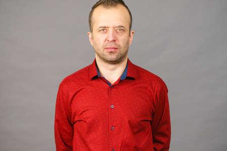 Happy joyful nice adult guy. Man with beard wearing red shirt on gray background. Stock Photo