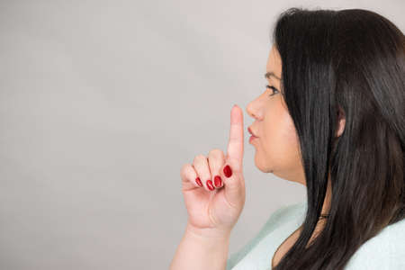 Adult woman asking for silence or secrecy with finger on lips, hush hand gesture, side view on grey, copy space text area Imagens