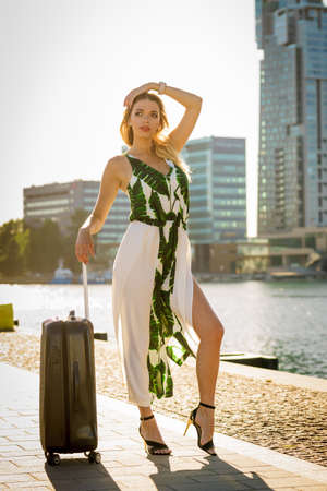 Fashionable woman arriving to new city. Beautiful fashion model holding her suitcase on wheels admiring town after arrival.