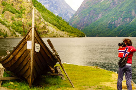 Female tourist with norwegian flag near old wooden viking boat on fjord shore, taking photo with camera. Tourism and traveling concept