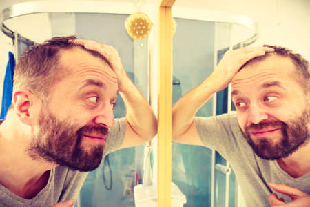 Happy man looking at his hair in bathroom mirror. Seeing improvement of hairline. Male haircare concept.