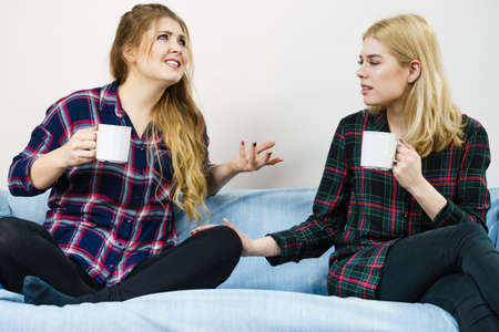 Two female friends sitting together on sofa chatting talking and drinking tea or coffee spending time together Reklamní fotografie