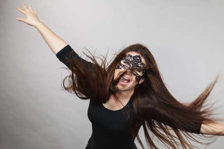 Happy pretty mysterious woman wearing black eye lace mask having tousled windblown long brown hair. Stock Photo