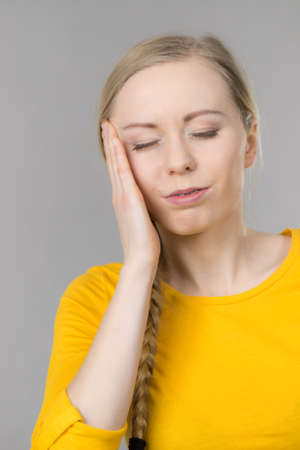 Young blonde woman having serious migrene suffering from horrible head ache feeling big pain.