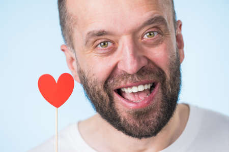Adult man being in love holding small red shape heart on stick. Romance, flirting, Valentines Day concept. Stock Photo