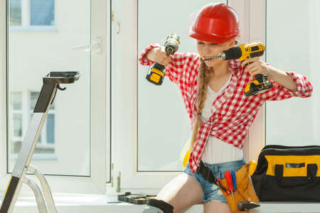 Young woman wearing helmet using power drill and tools for work at home, installing windows. Girl working at flat remodeling. Building, repair and renovation. Banco de Imagens