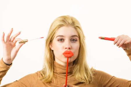 Młoda dorosła kobieta nakłada szminkę lub błyszczyk, robiąc makijaż, trzymając sztuczne usta na patyku
