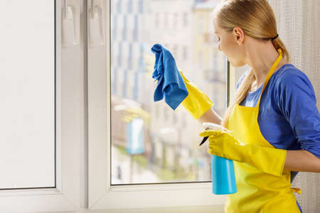 Young woman in yellow gloves cleaning window pane at home with rag and spray detergent. Cleaning concept Foto de archivo - 124548728