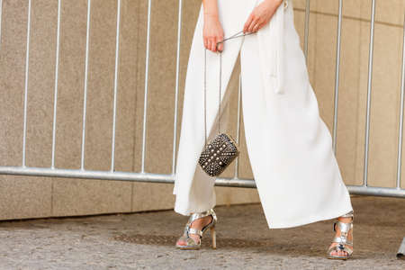 Unrecognizable woman wearing fashionable outfit. Close up at silver high heels, white culottes trousers and small black bag purse with pearls