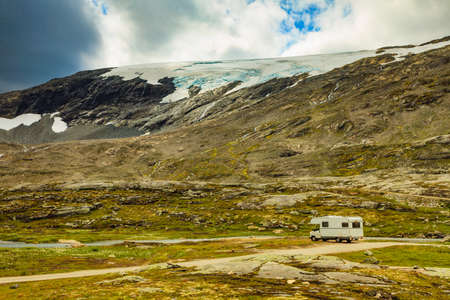 Camper car in norwegian mountains. Camping on nature. Traveling, holidays and adventure concept. Reklamní fotografie