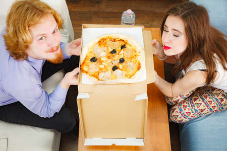 Young couple of friends spending time together drinking beer and eating italian food, delicious pizza meal. Relaxing at home. Stock Photo