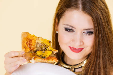 Young woman eating hot fresh pizza slice. Delicious fast food meal. People, italian cuisine concept.