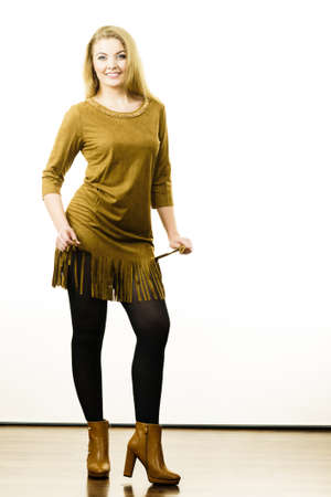 Fashionable woman wearing long khaki vintage dress, black leggings and brown high heels boots. Autumnal outfit concept.