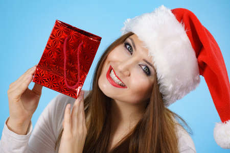 Young adult pretty woman is happy to give Christmas gifts. Female wearing red Santa Claus hat holding presents. Blue background Stock Photo