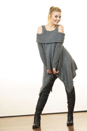 Woman in ponytail wearing gray long top sweater tunic, black tights. Stylish, autumnal outfit. 版權商用圖片