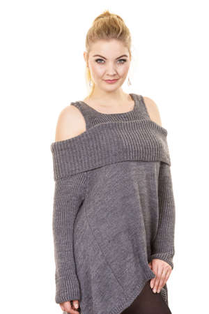 Woman in ponytail wearing gray long top sweater tunic with holes on shoulders. Stylish, autumnal outfit.