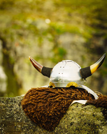 Equipment of viking or barbarian warrior outdoor on nature. Viking helmet on brown fur of animal in Norway. Tourism and traveling concept Imagens