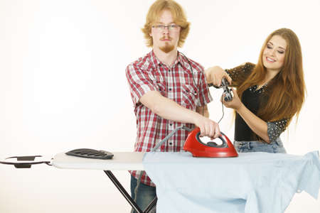 Woman being bossy having fun while steering man using gaming pad. Female controling her boyfriend to do ironing. Household duties concept. Stock Photo