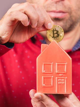 Man paying his house rent using cryptocurrency. Guy holding model of red home and bitcoin coin.