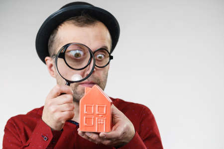 Funny looking adult man examining red model home using a magnifying glass, house inspection and real estate concept Stock Photo - 124961669