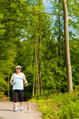 Healthy active retirement concept. Senior woman practicing nordic walking in forest park. Elderly female enjoying nature fresh air Imagens - 124961680