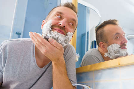 Man applying shaving foam cream on his face, standing in bathroom, looking at mirror, preparing to shave his face beard. Skincare Reklamní fotografie