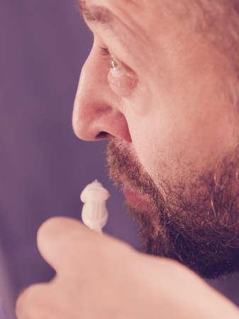 Adult man brushing his teeth looking at his bathroom mirror during morning hygiene routine. Banco de Imagens